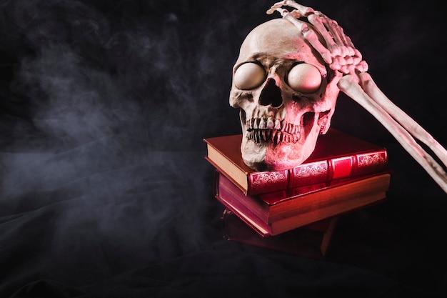 Crânio com globos oculares assustadores e braço esqueleto no topo