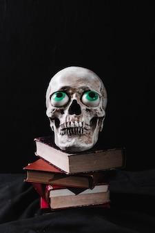 Crânio com globos oculares de brinquedo em livros empilhados