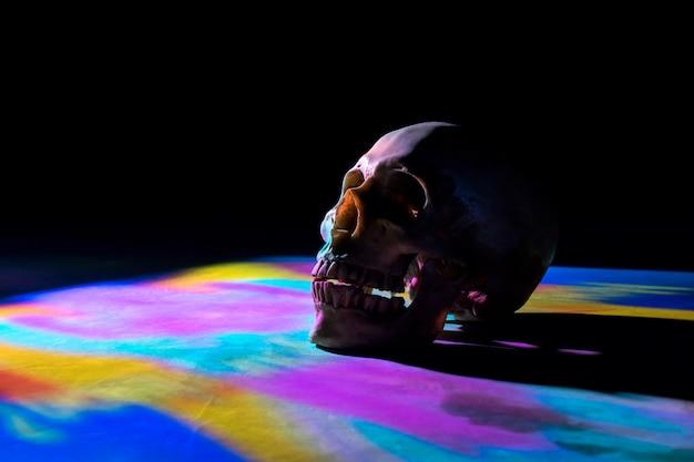 Crânio com iluminação colorida no fundo preto.