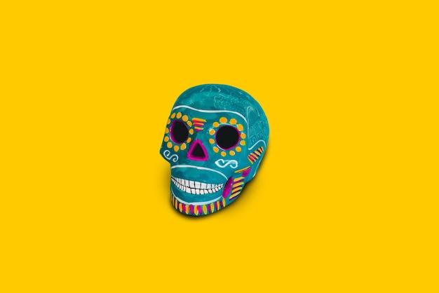 Crânio decorativo azul sobre fundo amarelo