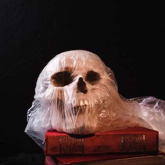 Crânio em saco de plástico na pilha de livro