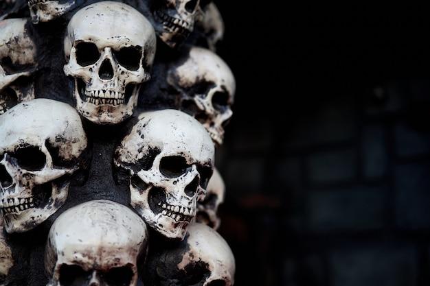 Crânio halloween background muitos crânios de pessoas ficam em cima uns dos outros. conceito assustador místico. memorial oculto de pesadelo abstrato