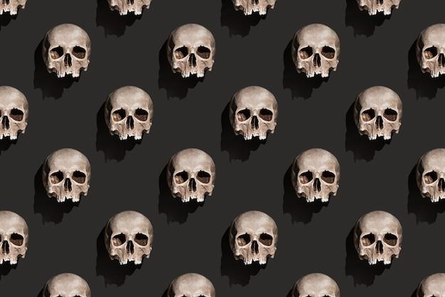 Crânio humano antigo com sombra no padrão abstrato de fundo preto.