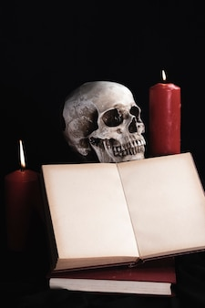 Crânio humano com maquete do livro e velas