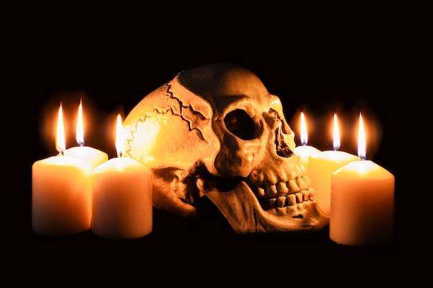 Crânio humano de perfil entre velas acesas no escuro, ainda vida assustadora, altar.