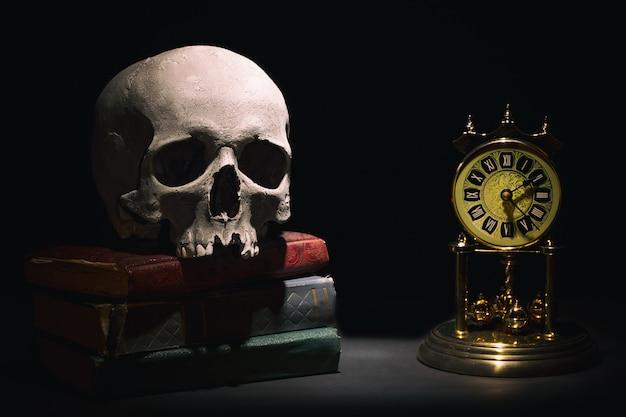 Crânio humano em livros antigos perto de relógio vintage retrô em fundo preto sob o feixe de luz.
