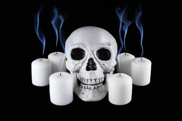Crânio humano entre velas apagadas brancas com plumas azuis de fumaça no escuro, natureza morta assustadora, altar.