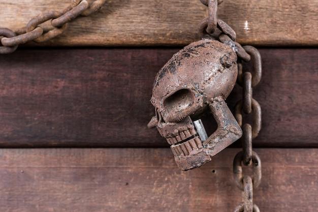 Crânio metálico com corrente em fundo de madeira