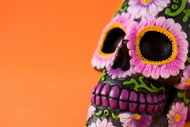 Crânio mexicano típico com flores pintadas em fundo laranja