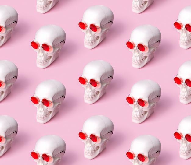 Crânio no padrão sem emenda de óculos de sol na mesa rosa pastel.