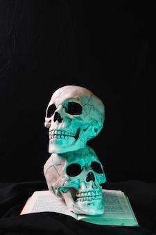 Crânios iluminados no livro aberto
