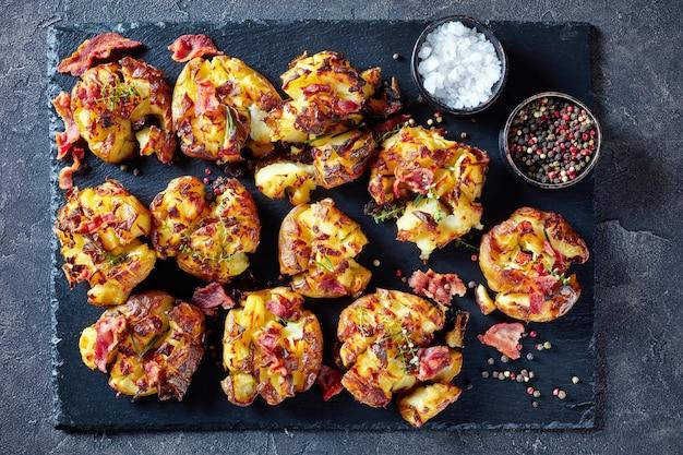 Crash hot new potatoes polvilhadas com especiarias, bacon frito e ervas em uma bandeja de ardósia em uma mesa de concreto, culinária australiana, visão horizontal de cima, flatlay, close-up