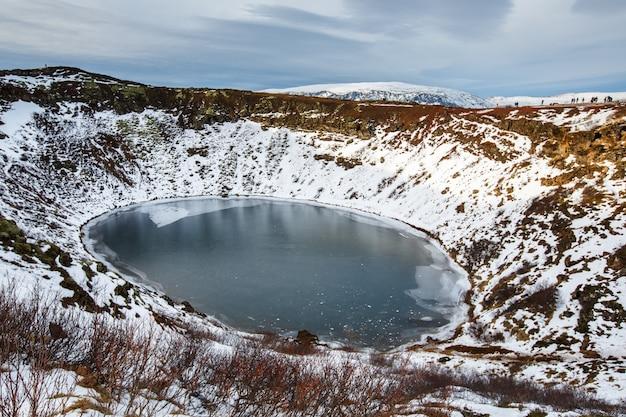 Cratera vulcânica no inverno sob céu nublado