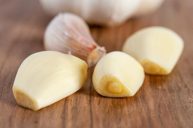 Cravinho de alho e cebola na placa de madeira com comida branca e saudável