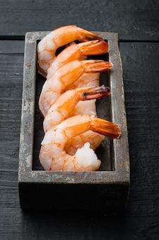 Cravo de camarão gigante descascado com cauda, em caixa de madeira, sobre mesa de madeira preta