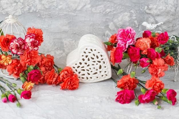 Cravos brilhantes e coração de cerâmica sobre um fundo cinza