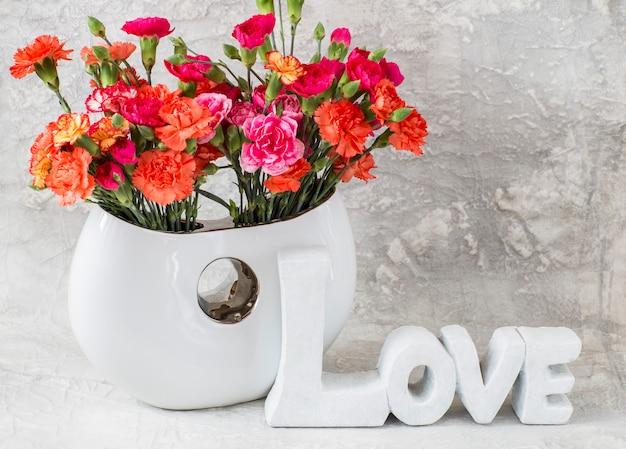 Cravos brilhantes em um vaso branco sobre um fundo cinza e a palavra amor