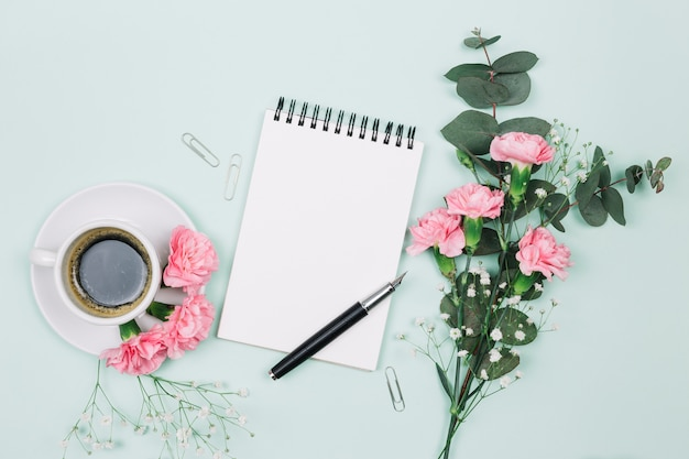 Cravos cor-de-rosa e flores de gypsophila com copo de café; bloco de notas em espiral e caneta-tinteiro em pano de fundo azul