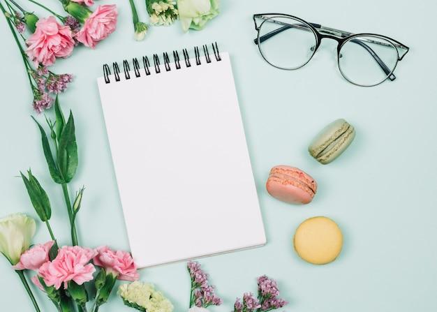 Cravos cor-de-rosa e flores do limonium perto do bloco de notas espiral; óculos e macaroons em pano de fundo azul