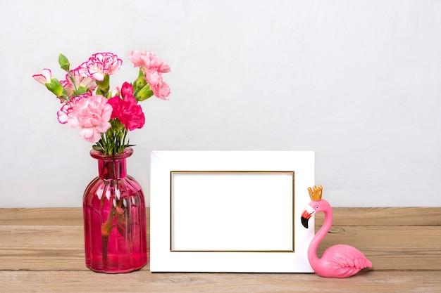 Cravos cor de rosa pequenos em um vaso e moldura branca, uma figura de flamingo na madeira