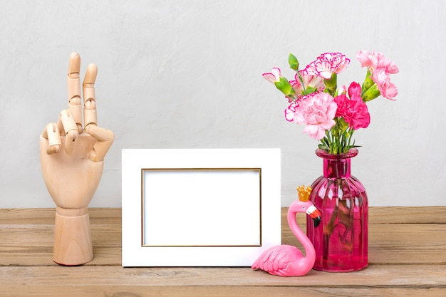 Cravos cor de rosa pequenos em vaso, moldura branca, figura de flamingo, mão de madeira na mesa de madeira e parede cinza