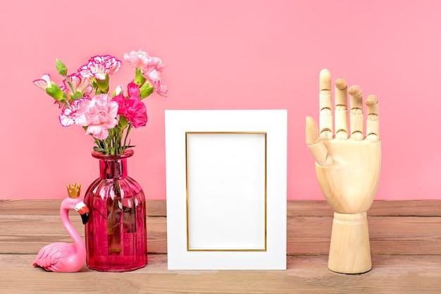 Cravos cor de rosa pequenos em vaso, moldura branca, figura de flamingo, mão de madeira na mesa de madeira e parede rosa