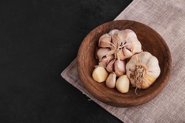 Cravos-da-índia de alho em uma xícara de madeira, vista de cima.