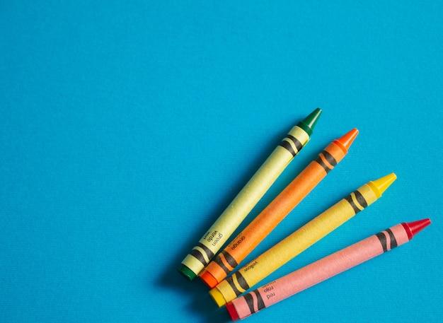 Crayons childs coloridos em fundo azul texturizado com espaço de cópia à esquerda