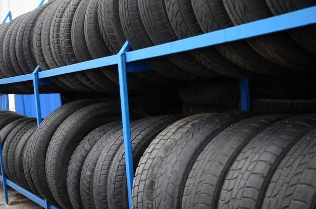 Cremalheira com variedade de pneus de carro na loja de automóvel. muitos pneus pretos. fundo de pilha de pneus. foco seletivo