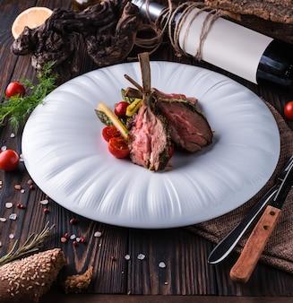 Cremalheira de cordeiro com ervas provençais em um grande prato branco.
