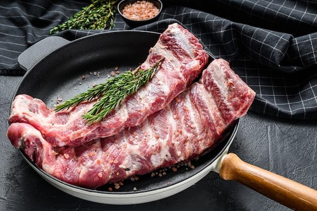 Cremalheira de entrecosto de porco cru cru temperado com especiarias em uma panela.