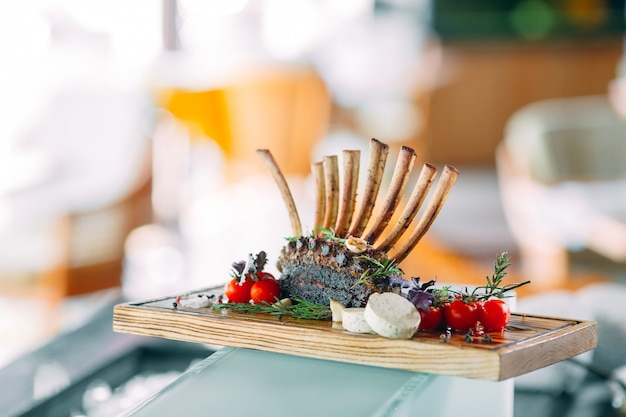 Cremalheira de prato de cordeiro com tomates em uma bandeja de madeira.