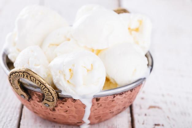 Creme branco, bolas de sorvete em uma tigela de metal autêntica