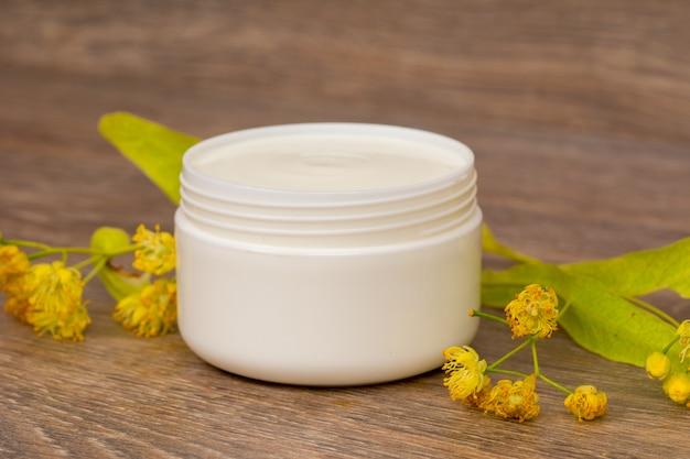 Creme corporal aberto frasco de plástico com flores de camomila e tília na mesa de madeira