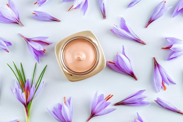 Creme corporal de açafrão e muitas belas flores roxas de açafrão em um fundo branco. o uso do açafrão em cosmetologia natural.