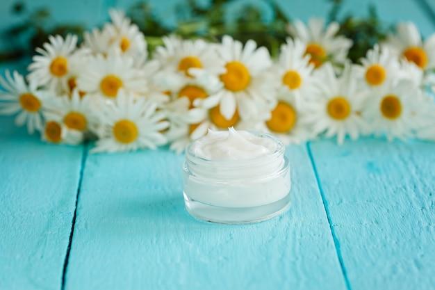 Creme cosmético com flor de camomila ou um corpo e rosto na mesa de madeira azul