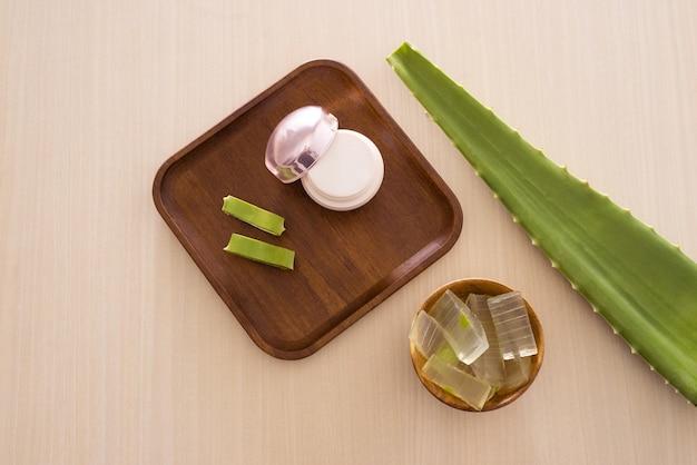 Creme cosmético de aloe vera na bandeja de madeira com folha de aloe vera e tigela sobre fundo claro.