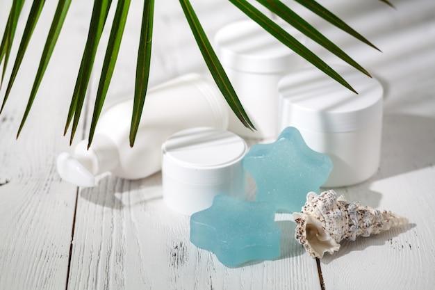 Creme cosmético e recipientes de belo spa na mesa branca