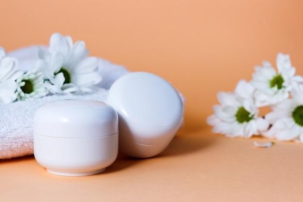 Creme cosmético em tubos brancos ou frascos em um fundo bege com flores brancas