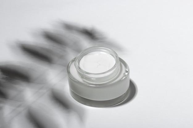 Creme cosmético ou máscara em um frasco de vidro com sombras duras das folhas em um fundo branco. cuidado orgânico natural para a pele do rosto e do corpo. vista de cima.
