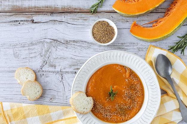 Creme de abóbora caseiro e saudável com pão de cima na mesa de madeira. postura plana
