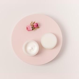 Creme de beleza rosado em frasco com tampa e flores rosas em pódio redondo