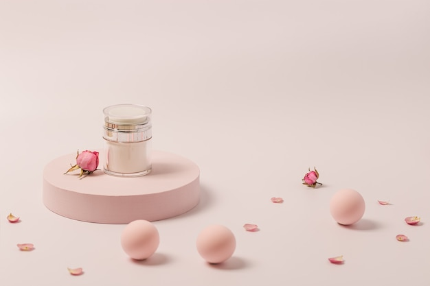 Creme de beleza rosado em pote e flores rosas em pódio redondo