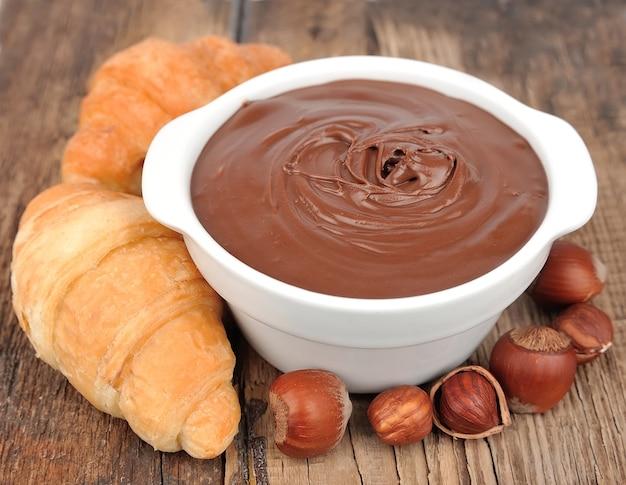 Creme de chocolate com croissants e avelã na mesa de madeira