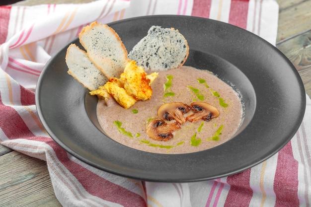 Creme de cogumelos na tigela escura. sopa cremosa caseira com cogumelos boletus fatiados.