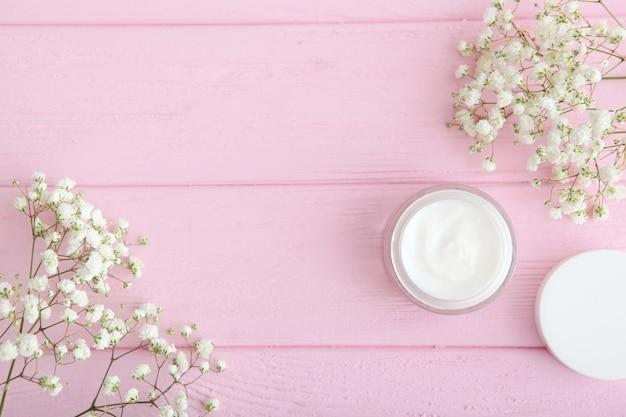 Creme de cuidados e flores em um fundo colorido vista de cima cosméticos para cuidados com a pele