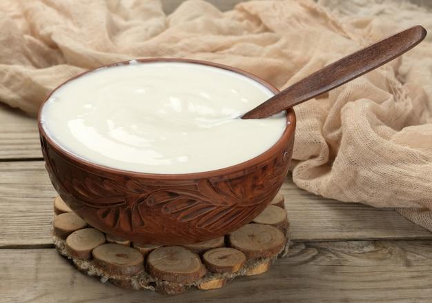 Creme de leite em uma tigela de cerâmica marrom com uma colher de pau sobre uma superfície de madeira, produto útil de leite fermentado, vista de cima
