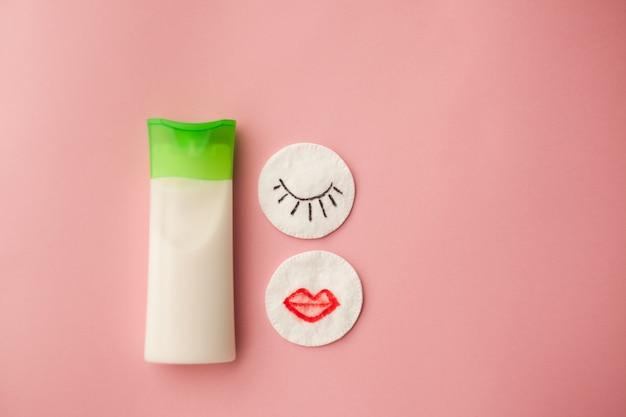 Creme de limpeza para o rosto e uma almofada de algodão com um remuver. fundo rosa. remoção de maquiagem.