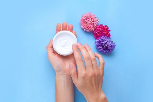 Creme de mãos hidratante e flores. cuidados com as mãos. eliminação da pele seca das mãos.