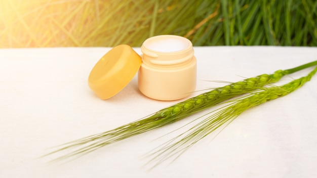 Creme de pele hidratante com espiguetas verdes em um carrinho branco nos raios de sol, cosméticos para cuidados com o corpo, beleza, spa.